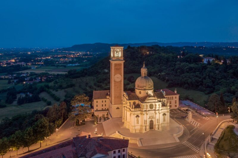 Monte Berico church lit up at night with countryside and city lights in background