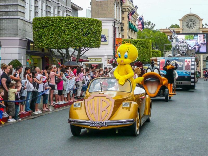 Movieworld parade on the Gold Coast with tweety bird in a car in front and people lining road and watching