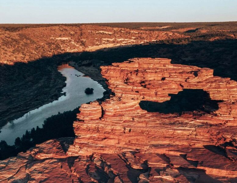 Sunset over orange rock gorge with river flowing through it at Kalbarri in Western Australia