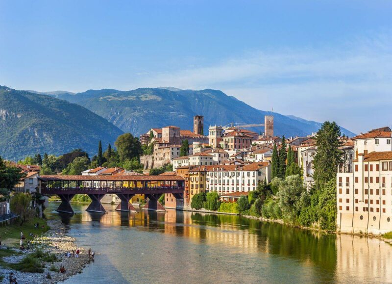 Old Bridge over river with historic buildings and mountains in background in Bassano - one of the best day trips from Venice