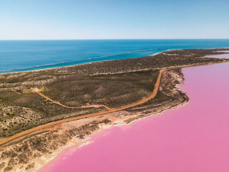 Aerial view over pink lake, sandy strip of land and ocean on the other side in Western Australia