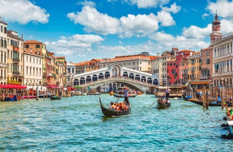 Rialto Bridge over Grand Canal with gondolas on canal and historic buildings on each side - add Rialto Bridge to your Venice Itinerary