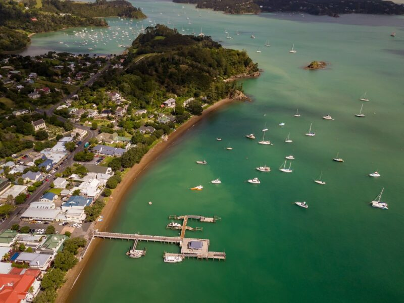 Aerial view over ocean, wharf, and buildings in Russell - a visit here is one of the best things to do in Northland