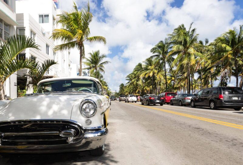 Classic car parked on side of road with palm trees and buildings lining the street in Miami