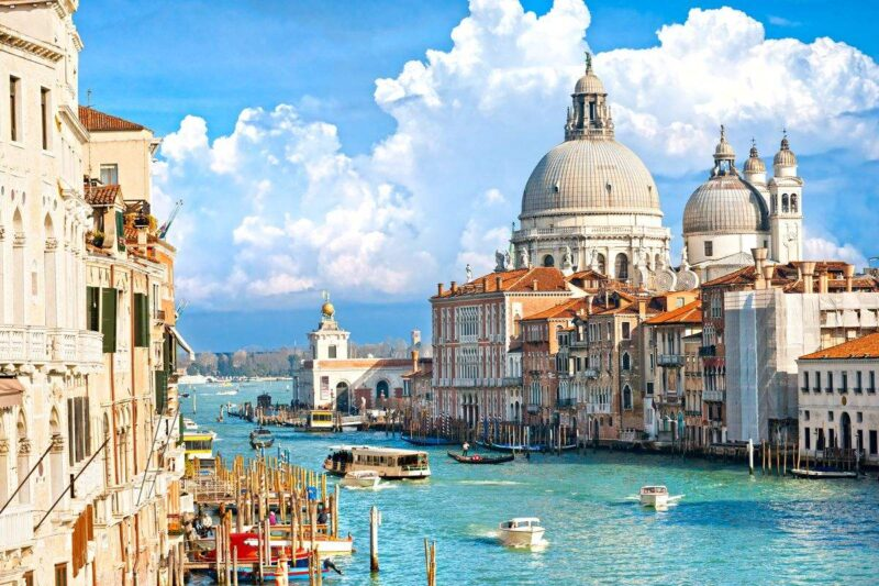 Grand Canal with historic buildings on each side on a sunny day in Venice