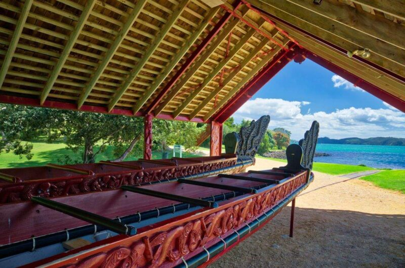 Waka canoe under shelter with ocean in background at Waitangi Treaty Grounds in Northland