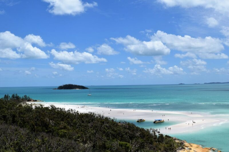 View over to Whitehaven Beach with small island in background and forested coastline in foreground - a visit to Whitehaven Beach is one of the best things to do in Queensland