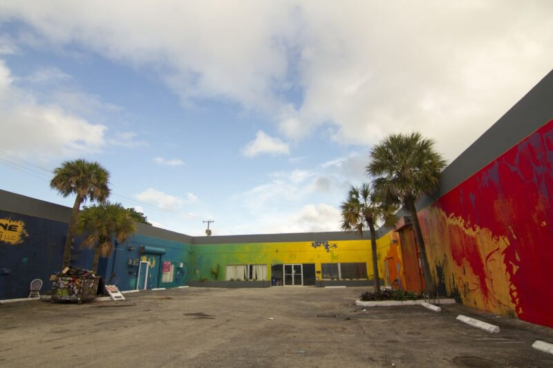 Colorfully painted walls in a U shape around concrete carpark and palm trees in Wynwood, Miami