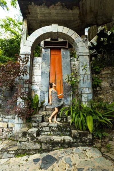 Nina standing on stairs in front of giant door and looking up at it at Las Pozas Xilitla Jardin on a Huasteca Potosina tour