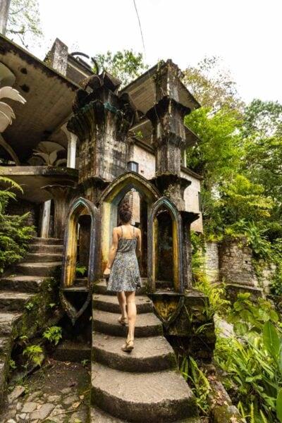 Nina walking up path leading up to unusual sculpture surrounded by foliage in Las Pozas Xilitla Jardin, Huasteca Potosina