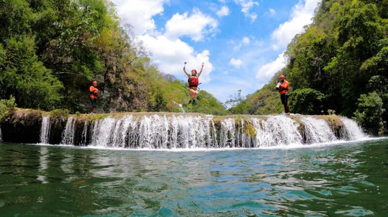 Three people in the air after jumping from Micos waterfall with pool below them on a Huasteca Potosina tour