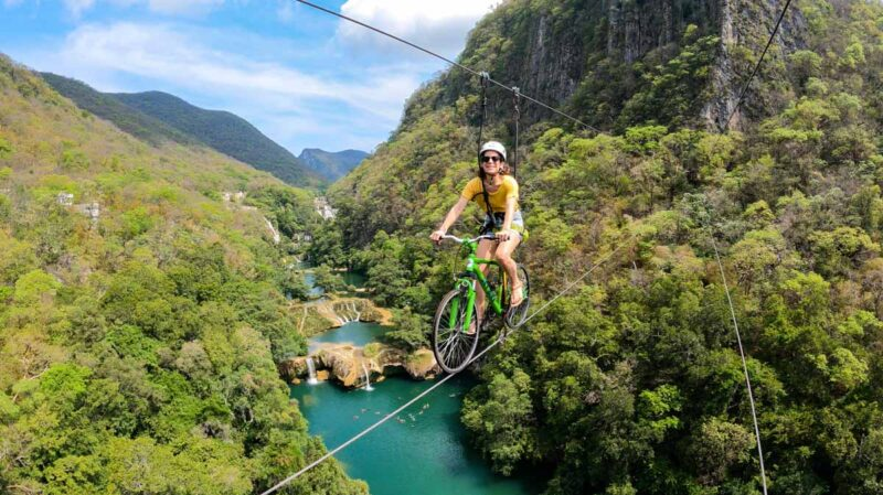 Nina riding a bike on a zipline with views of Micos waterfall and jungled mountains in background - this is one of the Huasteca Potosina tours in Mexico