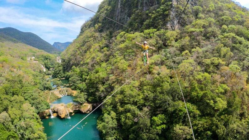 View of person biking on a zipline above a blue pool and jungled mountains on a Huasteca Potosina tour
