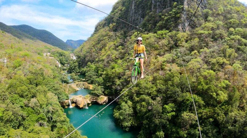 Perspn on skybike on zipline over Micos Waterfall and jungled mountains in Huasteca Potosina