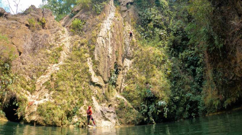 People rappeling down cliff with water at the bottom on one of the Huasteca Potosina tours