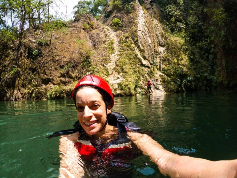 Nina in water with helmet and lifejacket on with cliff in background on one of the adventurous Huasteca tours