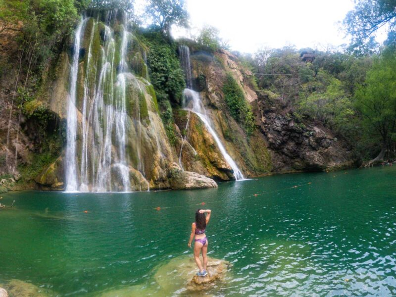 Nina standing on rock in waterfall pool looking at Minas Viejas waterfall in front of her on one of the Huasteca Potosina tours