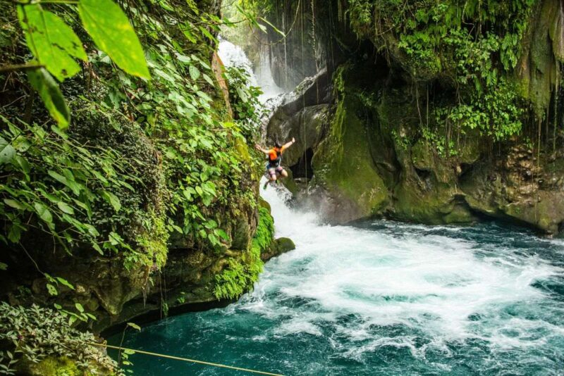 Person in midair jumping from Puente De Dios Falls with pool below and green mossy rocks on each side