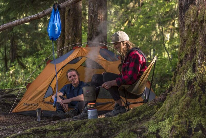 LifeStraw Flex Advanced Gravity Water Filter hanging at campsite with two people sitting around in front of orange tent - one of the best travel water filters