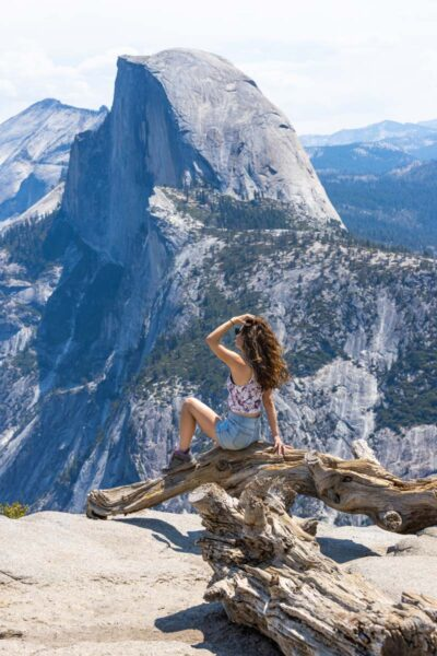 Woman sitting on log at Glacier Point with view of the mountain in Yosemite