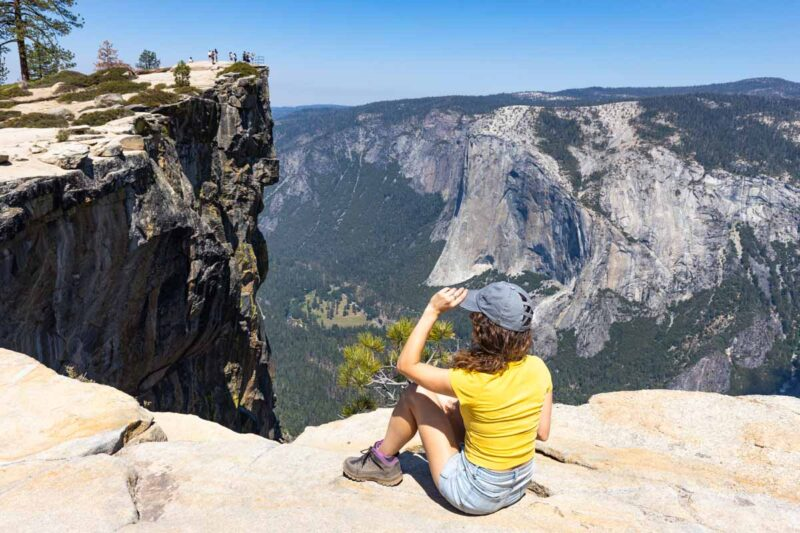 Woman sitting on cliff at Taft Point in Yosemite National Park